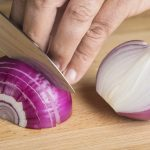 Chef chopping a red onion with a knife